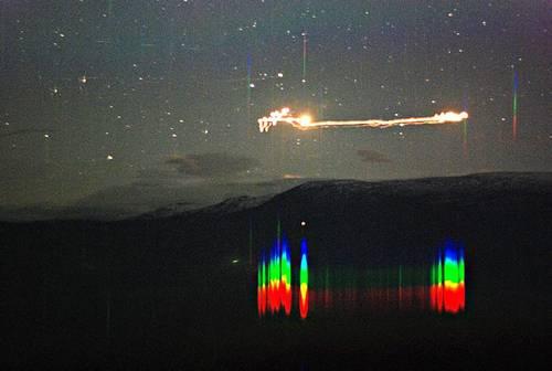 ekst:    Dette bildet av  Hessdalsfenomenet er tatt med 30 sekunders eksponeringstid klokken 10 en septemberkveld 2007 i forbindelse med Science Camp i Hessdalen.    De flerfargete strekene under er det optiske spekteret til lyset, og skal nå analyseres for å se hvilke grunnstoffer som går igjen. Farten er anslått til godt over 400 meter i sekundet.    Foto: Bjørn Gitle Hauge     © ScienceCenter Østfold